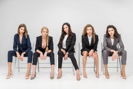 Photo for Successful women in formal wear sitting on chairs isolated on grey - Royalty Free Image