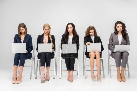 atractivas mujeres jóvenes usando computadoras portátiles mientras están sentadas en sillas aisladas en gris