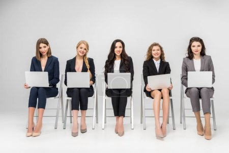 cheerful young women using laptops while sitting on chairs isolated on grey