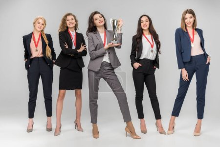 cheerful businesswoman holding trophy and standing near attractive colleagues on grey background