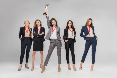 cheerful businesswoman holding trophy above head and standing near attractive colleagues posing on grey background