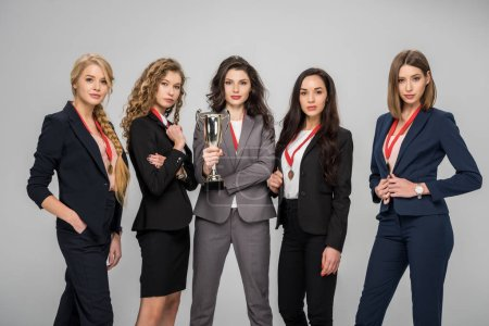 Photo for Successful businesswomen holding trophy and standing isolated on grey - Royalty Free Image