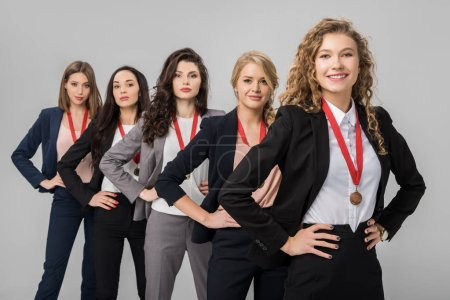 Photo for Selective focus of cheerful businesswomen standing with medals isolated on grey - Royalty Free Image