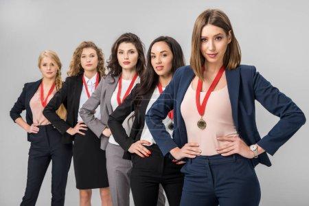 Photo pour Mise au point sélective des femmes d'affaires réussis debout avec médailles isolés sur fond gris - image libre de droit
