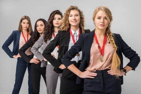 Photo pour Mise au point sélective des belles femmes d'affaires permanent avec médailles isolés sur fond gris - image libre de droit