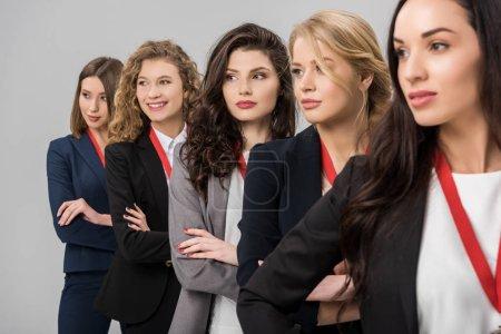 Photo pour Foyer sélectif de belles jeunes femmes d'affaires debout avec des médailles isolées sur gris - image libre de droit