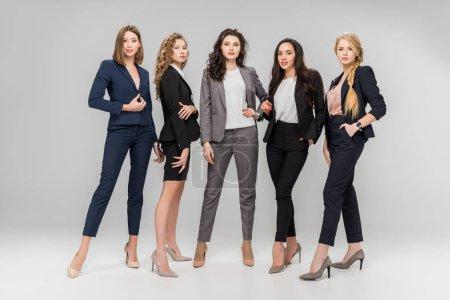 Photo pour Belles femmes ayant réussi debout avec les mains dans les poches, sur fond gris - image libre de droit