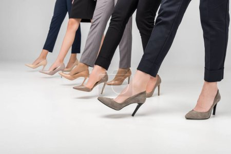 Photo for Cropped view of businesswomen walking in high heel shoes on grey background - Royalty Free Image