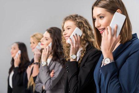 Foto de Enfoque selectivo de sonrientes mujeres empresarias hablando por teléfonos inteligentes aislados en gris - Imagen libre de derechos