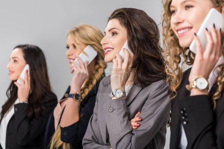 Photo pour Mise au point sélective des femmes d'affaires gais parler sur les smartphones près isolés sur gris - image libre de droit
