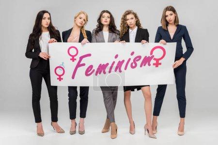 Photo pour Femmes d'affaires attrayants tient grande pancarte avec lettrage de féminisme sur fond gris - image libre de droit