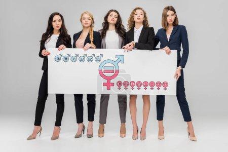 Photo pour Réussies jeunes femmes tenant le grand panneau avec le symbole de l'égalité entre les sexes sur fond gris - image libre de droit