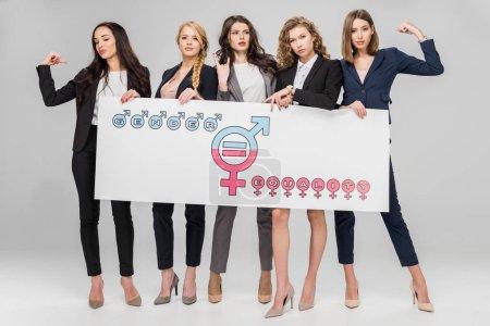 Photo pour Jeunes femmes d'affaires portant un grand signe avec un symbole d'égalité des sexes sur fond gris - image libre de droit