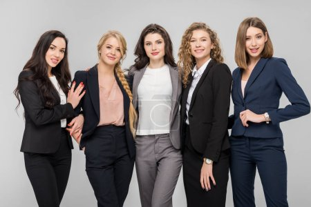 Photo for Beautiful young businesswomen standing and smiling isolated on grey - Royalty Free Image