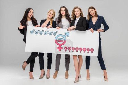 Photo pour Joyeuses jeunes femmes tenant le grand panneau avec le symbole de l'égalité entre les sexes sur fond gris - image libre de droit