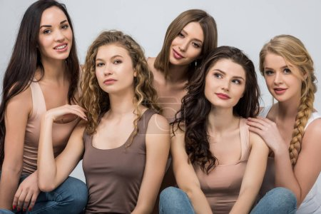 Photo for Attractive young women support each other isolated on grey - Royalty Free Image