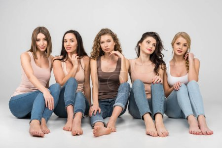 Photo for Attractive young women sitting together on grey background - Royalty Free Image