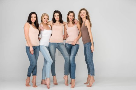 Photo for Happy young women hugging while standing together on grey background - Royalty Free Image