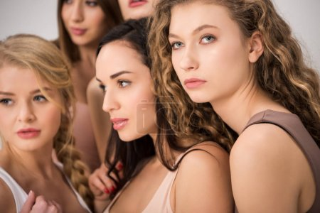 Photo for Selective focus of attractive women standing together while support each other isolated on grey - Royalty Free Image