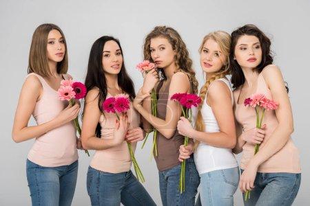 hermosas chicas sosteniendo flores de color rosa y de pie aislado en gris