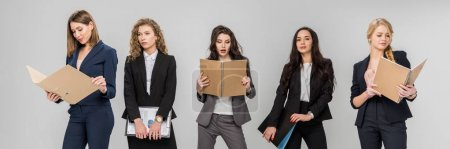 Photo for Attractive young businesswomen holding clipboards and folders while standing isolated on grey - Royalty Free Image