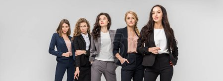 Photo for Beautiful young women standing with hands in pockets isolated on grey - Royalty Free Image