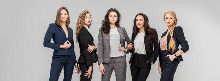 Photo pour Belles femmes ayant réussi debout avec les mains dans les poches isolées sur fond gris - image libre de droit