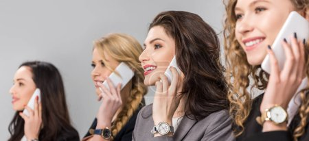 Photo for Selective focus of cheerful girls talking on smartphones isolated on grey - Royalty Free Image