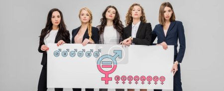 Photo pour Jeunes femmes réussies portant un grand signe avec le symbole de l'égalité des sexes isolé sur gris - image libre de droit