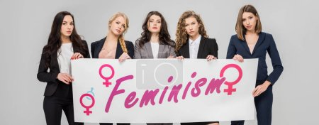 Photo pour Femmes d'affaires attrayants tient grande pancarte avec lettrage de féminisme isolé sur fond gris - image libre de droit