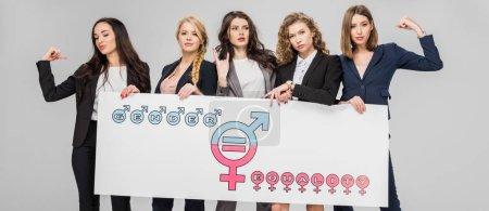 Photo pour Jeunes femmes d'affaires portant un grand signe avec le symbole de l'égalité des sexes isolé sur gris - image libre de droit