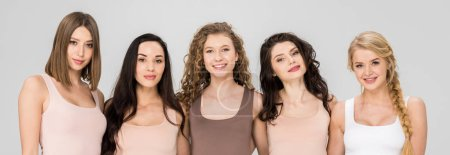 Photo for Happy girls embracing while standing together isolated on grey - Royalty Free Image