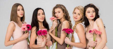 Foto de Beautiful female friends holding pink flowers and standing isolated on grey - Imagen libre de derechos