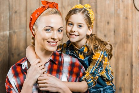 Photo for Cute daughter hugging cheerful mother near wooden fence - Royalty Free Image