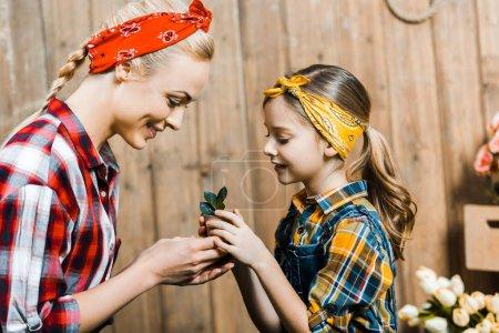 Photo pour Heureuse mère et la fille tenant la petite plante aux feuilles vertes - image libre de droit