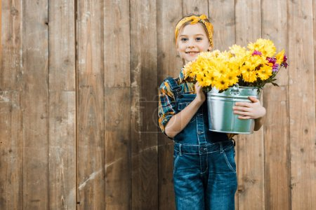 happy kid holding flowers in bucket and standing near wooden fence