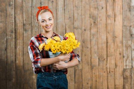 Photo pour Belle femme tenant des fleurs dans le seau et souriant près de clôture en bois - image libre de droit