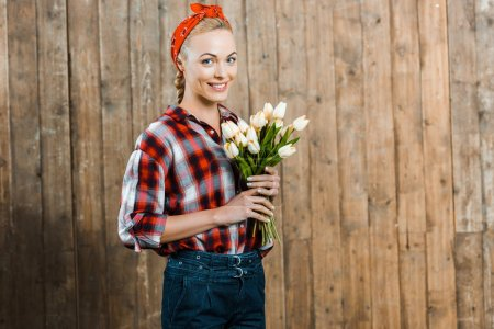 Photo for Cheerful woman smiling while holding tulips in hands - Royalty Free Image