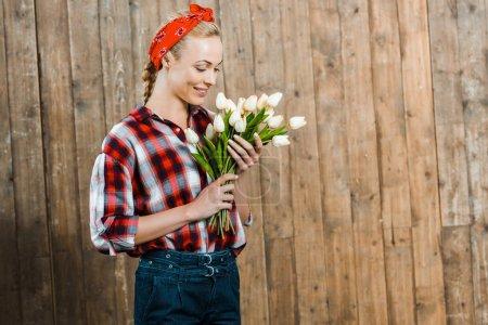 Photo pour Femme joyeuse, souriant tout en regardant les tulipes - image libre de droit