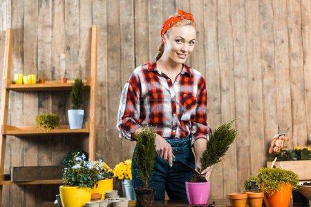 Photo pour Femme tenant pelle tout en transplantant des plantes en pot - image libre de droit