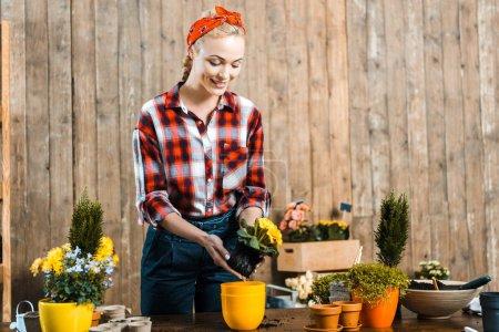 Photo pour Heureuse femme debout près de table et le repiquage des fleurs en pot - image libre de droit