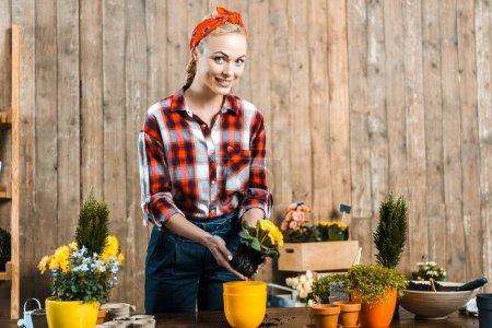 Photo pour Femme joyeuse, repiquage des fleurs en pot près de clôture - image libre de droit