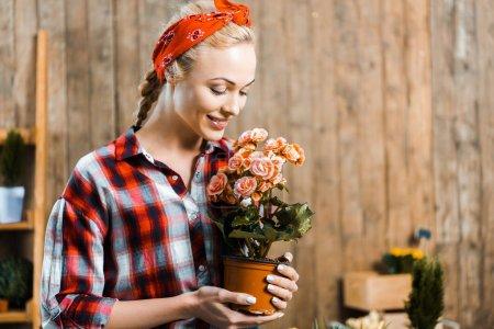Photo pour Femme joyeuse permanent et en regardant de pot de fleurs - image libre de droit