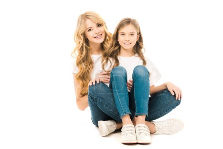 Photo for Smiling mother and daughter sitting on floor and looking at camera on white background - Royalty Free Image