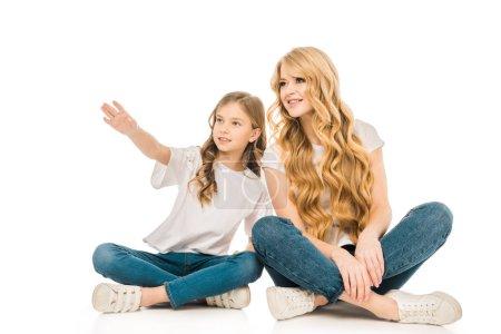 Foto de Lindo niño señalando la mano sentado en el piso junto a la madre sobre fondo blanco - Imagen libre de derechos
