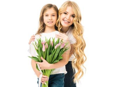 Photo pour Fille d'adorable embrassant heureuse mère tenant le bouquet de tulipes roses isolé sur blanc - image libre de droit