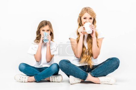 Photo for Mother and daughter sitting on floor with crossed legs and drinking coffee on white background - Royalty Free Image