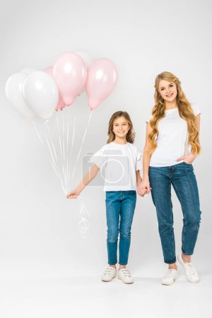 Photo for Cheerful child with festive air balloons holding hands with smiling mother on white background - Royalty Free Image