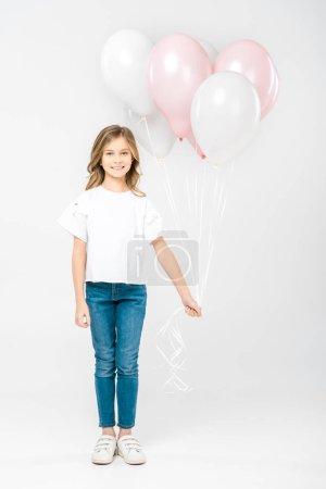Foto de Adorable child in white t-shirt and blue jeans holding festive air balloons on white background - Imagen libre de derechos