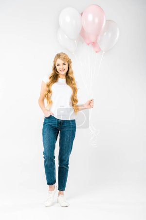 Photo for Smiling pretty woman with hand in pocket holding air balloons on white background - Royalty Free Image